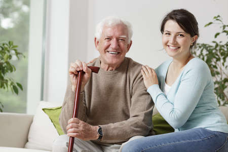 Photo pour Smiling old man holding a cane and smiling young woman - image libre de droit