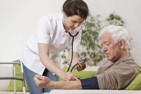 Foto de Young nurse taking old man's blood pressure - Imagen libre de derechos