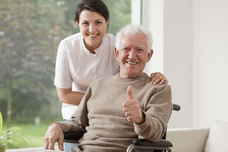 Photo pour Old man on wheelchair holding thumb up - image libre de droit