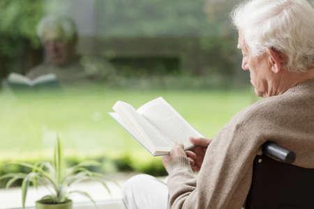 Photo pour Old man on wheelchair reading a book - image libre de droit
