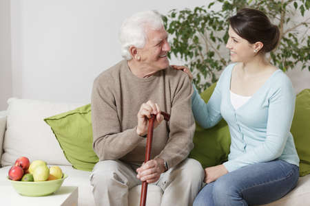 Foto de Old man holding a cane and smiling to young woman - Imagen libre de derechos