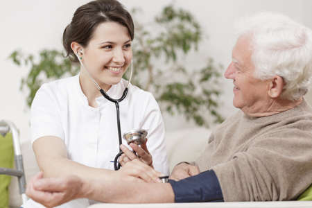 Photo for Smiling young nurse taking old man's blood pressure - Royalty Free Image