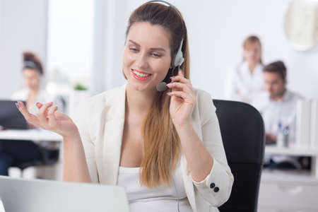 Photo pour Woman working in call center talking with customer - image libre de droit