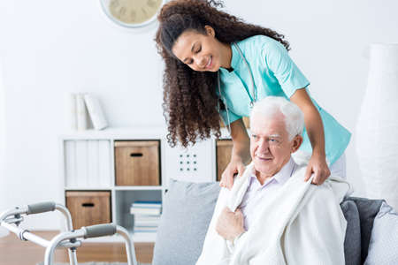 Foto per Young African American doctor helping senior man - Immagine Royalty Free