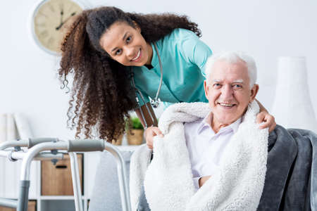 Photo pour Smiling doctor caring about patient at home - image libre de droit
