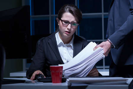Photo pour Sleepy woman working overtime in office - image libre de droit