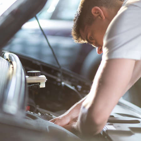 Photo pour Automobile mechanic repairing a car in service station - image libre de droit