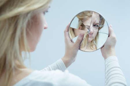 Photo pour Unhappy pretty girl with complexes and broken mirror - image libre de droit