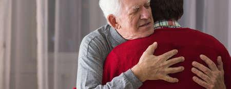 Photo pour Older grateful man hugging his helpful caregiver - image libre de droit
