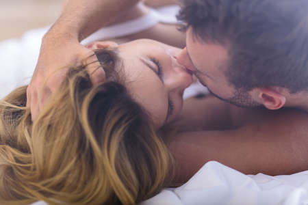 Photo pour Photo of sexy married couple kissing in bed - image libre de droit
