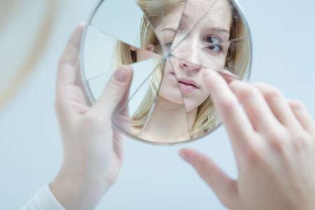 Foto de Insecure pretty young woman holding broken mirror - Imagen libre de derechos