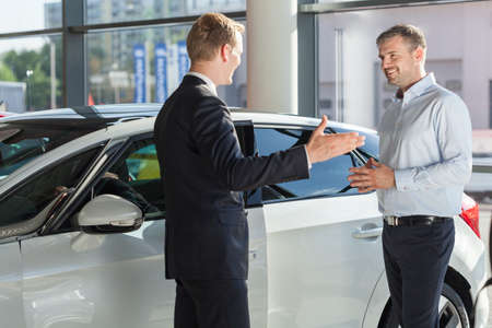 Photo pour Customer is smiling to his car dealer - image libre de droit