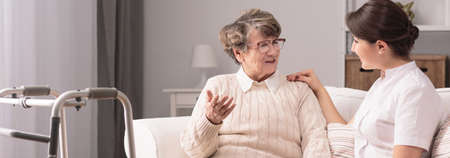 Foto de Senior older woman talking with female young caregiver - Imagen libre de derechos