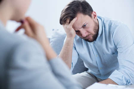 Foto de Photo of man with depression talking with counselor - Imagen libre de derechos