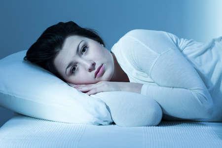 Foto de Troubled young woman in bed and lack of sleep - Imagen libre de derechos