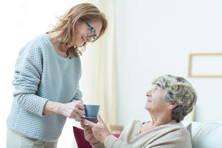 Photo pour Smiling senior care assistant helping elderly lady - image libre de droit