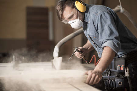Photo pour Horizontal view of professionally dressed carpenter varnishing a board - image libre de droit