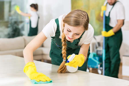Photo pour Smiling cleaning lady in yellow rubber gloves during work - image libre de droit