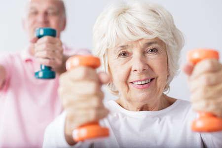 Foto de Older fit woman lifting two dumbbells - Imagen libre de derechos