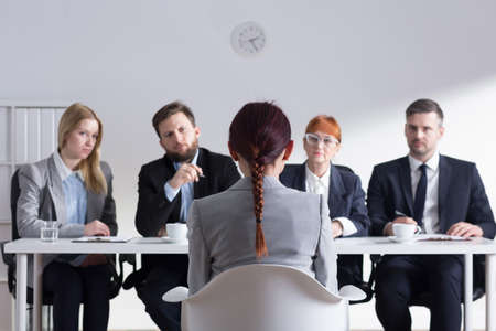 Photo pour Woman during job interview and four elegant members of management - image libre de droit