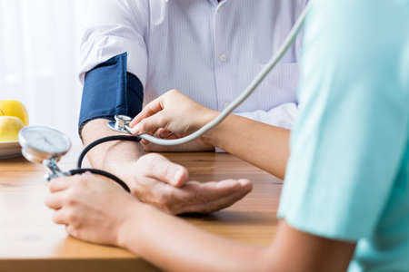 Foto per Close up of patient and doctor taking blood pressure - Immagine Royalty Free