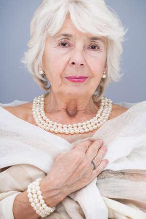 Foto de Elegant, senior woman with pearl necklace and bracelet, wearing white shawl - Imagen libre de derechos