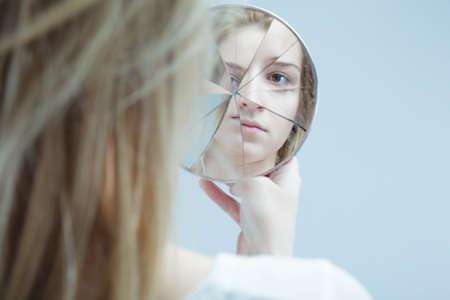 Foto de Image of woman with mental disorder holding broken mirror - Imagen libre de derechos