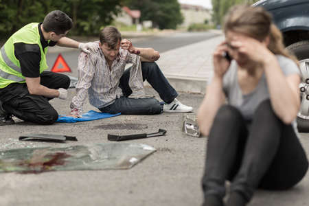 Foto de People sitting on the road after car crash - Imagen libre de derechos