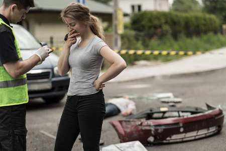 Foto de Young woman is terrified and telling policemen what happened - Imagen libre de derechos
