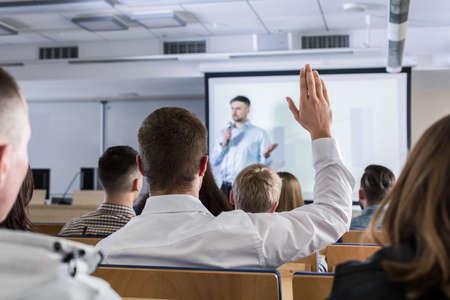 Photo pour Student raising hand during lecture - image libre de droit
