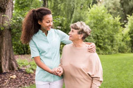 Photo pour Nurse is walking around with elder lady - image libre de droit