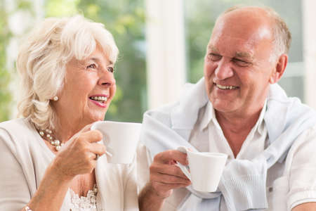 Photo pour Happy elderly married people smiling and drinking coffee - image libre de droit