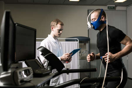 Foto per Athlete in oxygen mask running on treadmill and medic in white uniform - Immagine Royalty Free