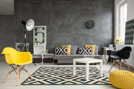 Photo pour Grey living room with sofa, chairs, standing lamp, small table, yellow details and pattern decorations in black and white - image libre de droit