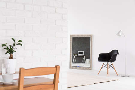 Photo pour Home interior with decorative mirror, chairs, standing lamp, wood table and white brick wall - image libre de droit
