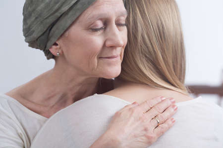 Photo pour Sick woman with cancer hugging her young daughter - image libre de droit
