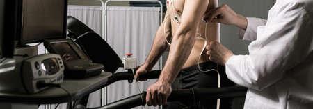 Foto de Cropped picture of a doctor checking electrodes on his patient's body - Imagen libre de derechos