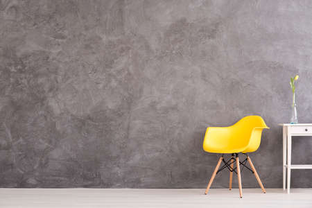 Foto de New yellow chair and small, decorative table standing in interior with grey wall - Imagen libre de derechos