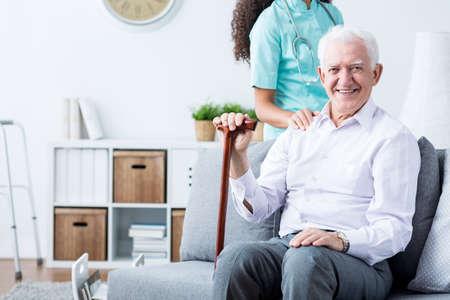 Foto de Happy senior disabled man with walking stick and caring young nurse - Imagen libre de derechos