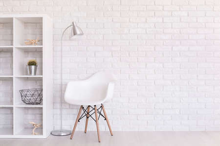 Photo for White regale with home decorations, standing lamp and modern chair standing in light room with brick wall design - Royalty Free Image