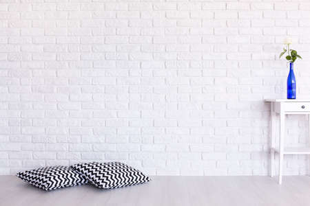 Photo pour Decorative, black and white pattern pillows and small table standing in white interior with brick wall design - image libre de droit