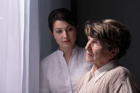 Foto de Sad older woman in nursing home waiting for relatives - Imagen libre de derechos