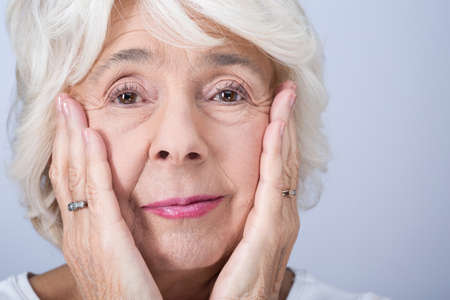 Foto per Portrait of older pretty woman with a few wrinkles. Touching her face with hands - Immagine Royalty Free