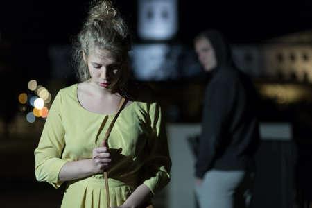 Photo pour Criminal observing young woman walking alone at night - image libre de droit