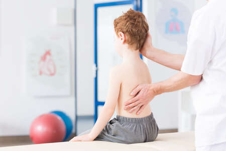 Photo for Little boy with scoliosis in rehabilitation clinic. Physiotherapist working with special method on boy's spinal column - Royalty Free Image