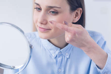 Foto de Woman inserting contact lens, sitting in front of a mirror - Imagen libre de derechos
