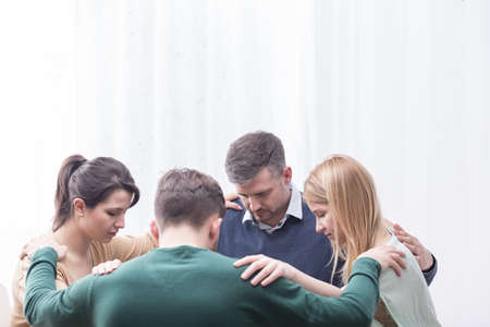 Photo pour Group of people holding each other at the shoulders forming circle - image libre de droit