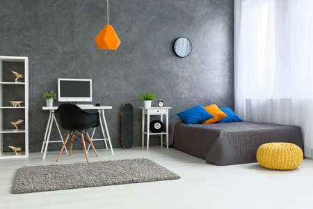 Foto de Cozy stylish bedroom designed for teenage boy. Grey walls and wooden floor. On the wall skate board and shelf with wooden models - Imagen libre de derechos