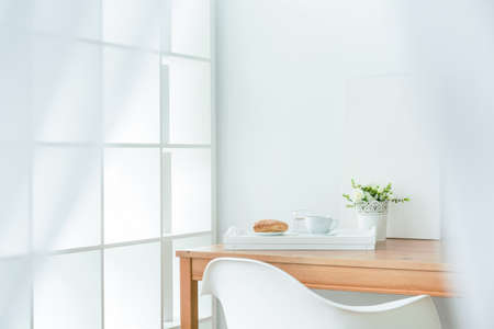 Foto de Wooden dining table in the corner of room. On it white tray with puff pastry and coffee - Imagen libre de derechos