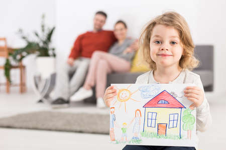 Photo pour Photo of a smiling little girl holding a drawing with a house, with her parents sitting on a sofa in the blurry background - image libre de droit